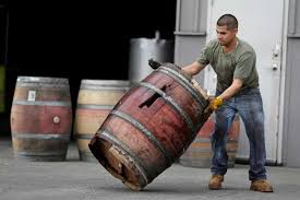 A worker removes an earthquake-damaged wine barrel from Napa Barrel Care Monday, Aug. 25, in Napa.